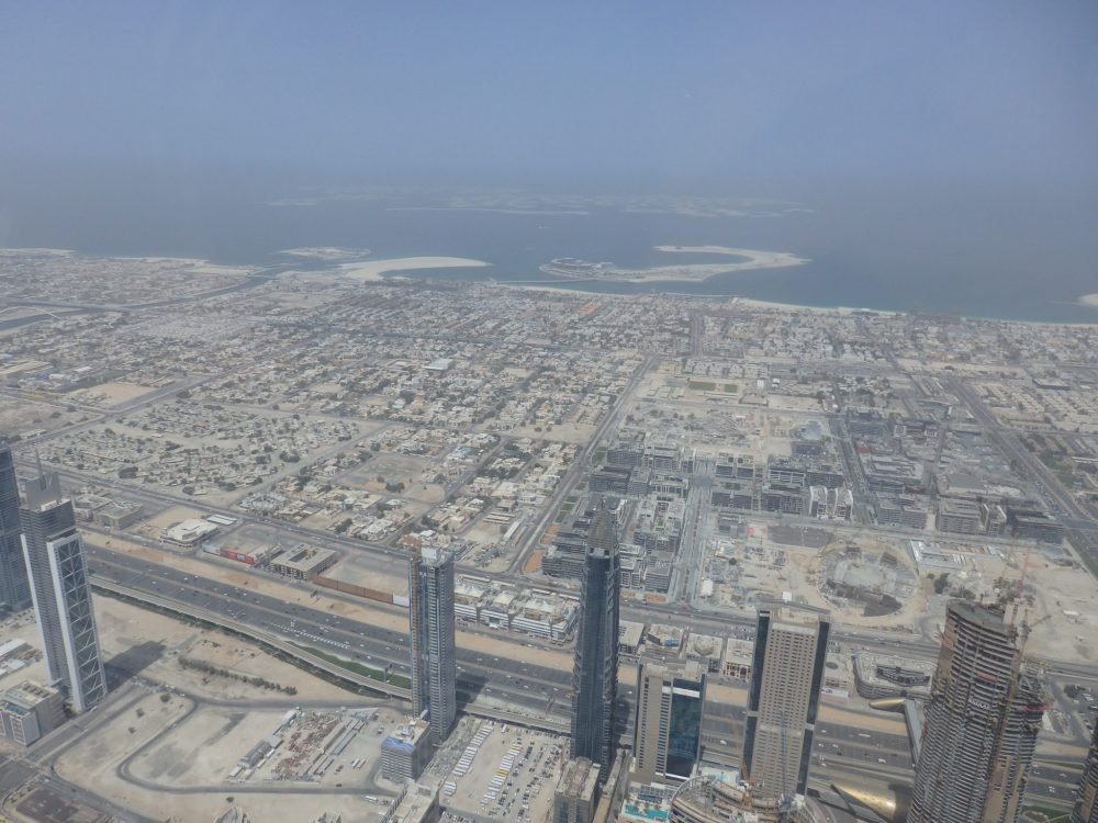 """Here you can see a lower-rise area of Dubai, mostly housing. In the dim distance is the coast, and beyond it are the artificial islands called the """"World Islands"""". Visiting Burj Khalifa"""