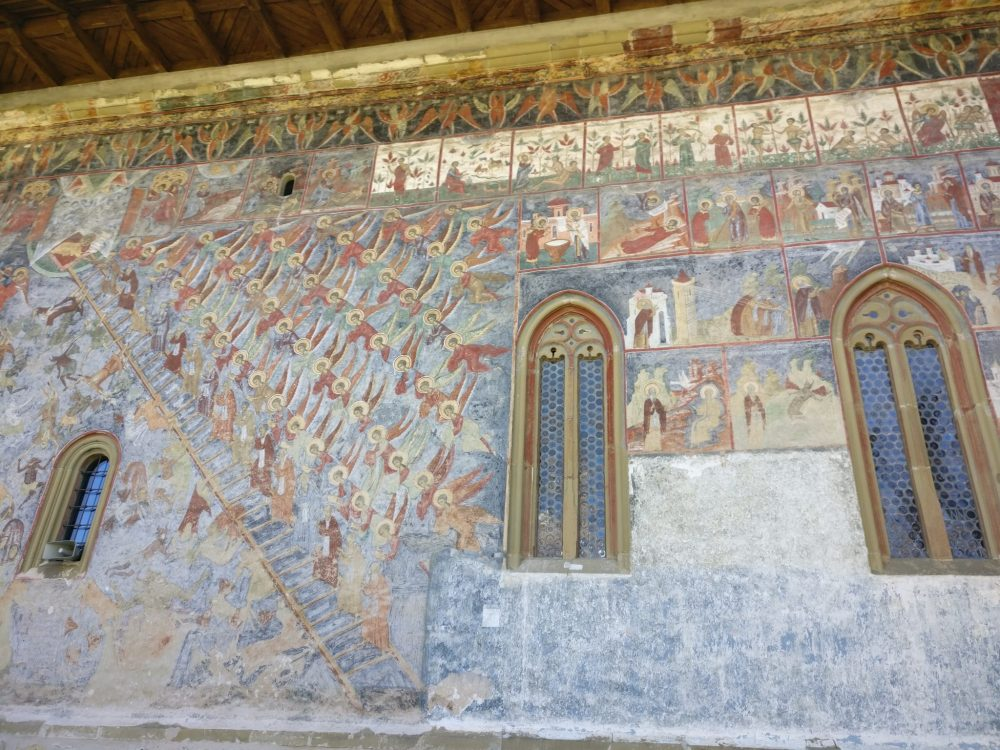 On this exterior wall, on the left, you can see a depiction of the Last Judgement. The winged and haloed watchers above, and the general chaos below. Notice that the devils are portrayed as black. Hmm. At the top, in the white panels, you can make out the Garden of Eden story. Spectacular painted churches of Moldavia.