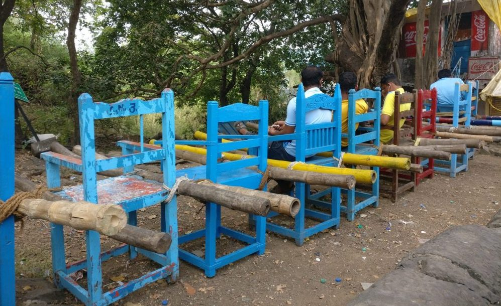 A row of bright blue wooden chairs stand with their back to the camera. EAch has two bamboo poles lashed to it with prope, one on either side of the seat. Men sit on some of the chairs. Elephanta Island travel guide.