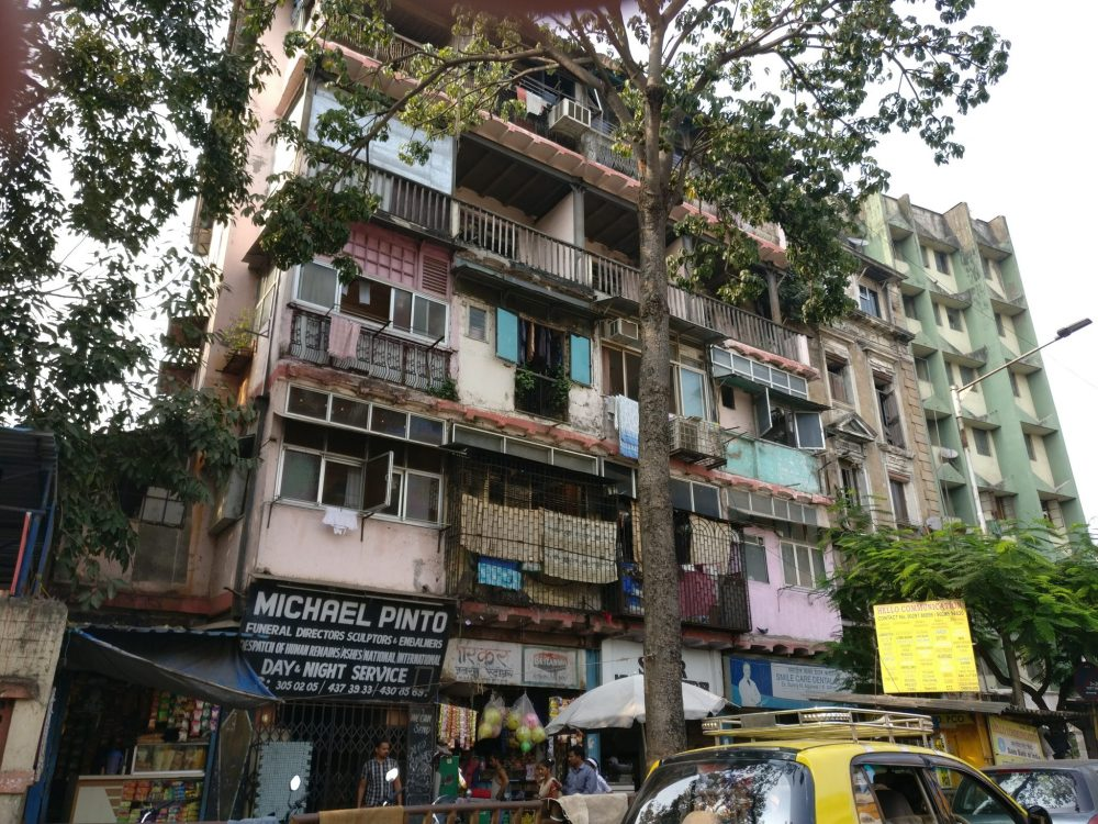 A block of flats somewhere in Mumbai, photographed out a car window.