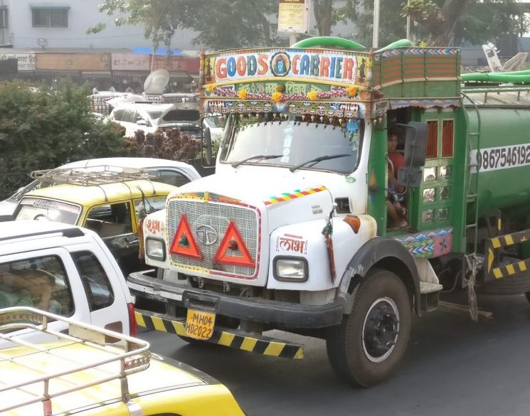a colorful truck in the traffic of Mumbai