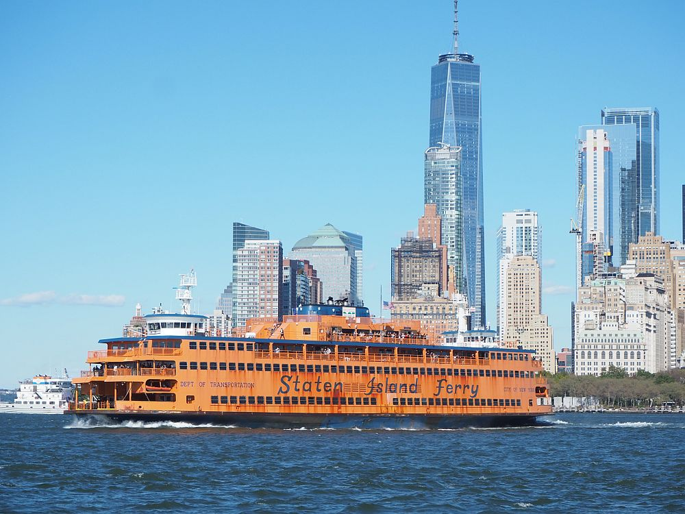 The Staten Island crossing dark blue water. The ship is a dirty orange color with a black hull. The sides are lined with square windows and at the end are some open spaces on each floor with railings at their edges. Behind the ship is part of the Manhattan skyline: a cluster of tall buildings. The Staten Island Ferry is a great way to see New York City on a budget.