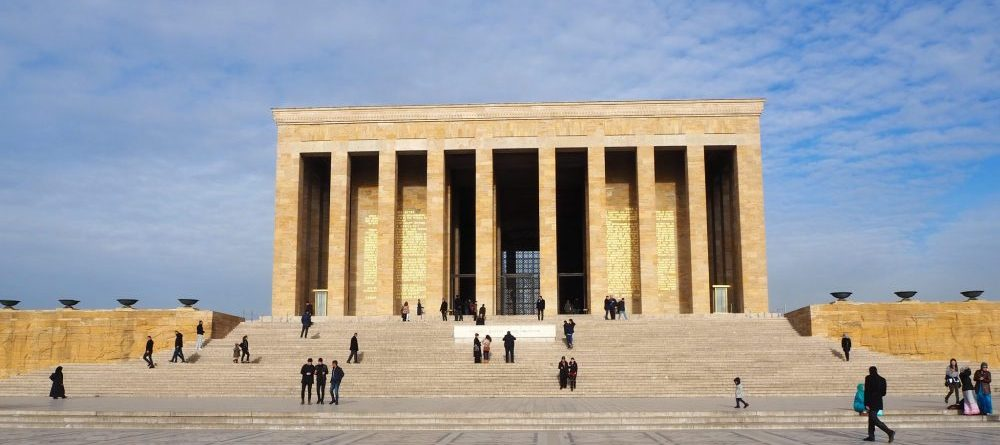 Anitkabir, the mausoleum of Ataturk in Ankara, Turkey stands at the top of a wide set of stairs - as wide as the building. The mausoleum is rectangular with a row of 10 square columns along the whole front. Behind that is mostly dark, but a window on the back side of the building is partly visible because a bit of light is coming through. Here and there on the stairs, at the base of the columns and nearer by on the plaza in front of the building are people.