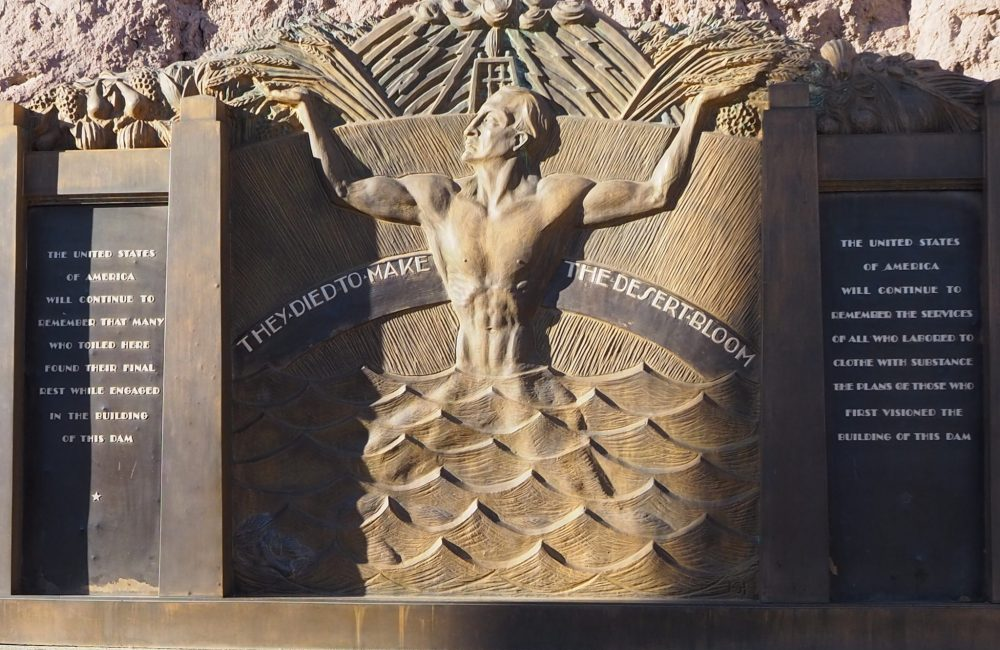 A bas-relief, it shows a naked man standing hip-deep in water, his hands raised. Words carved on either side read: They died to make the desert bloom.