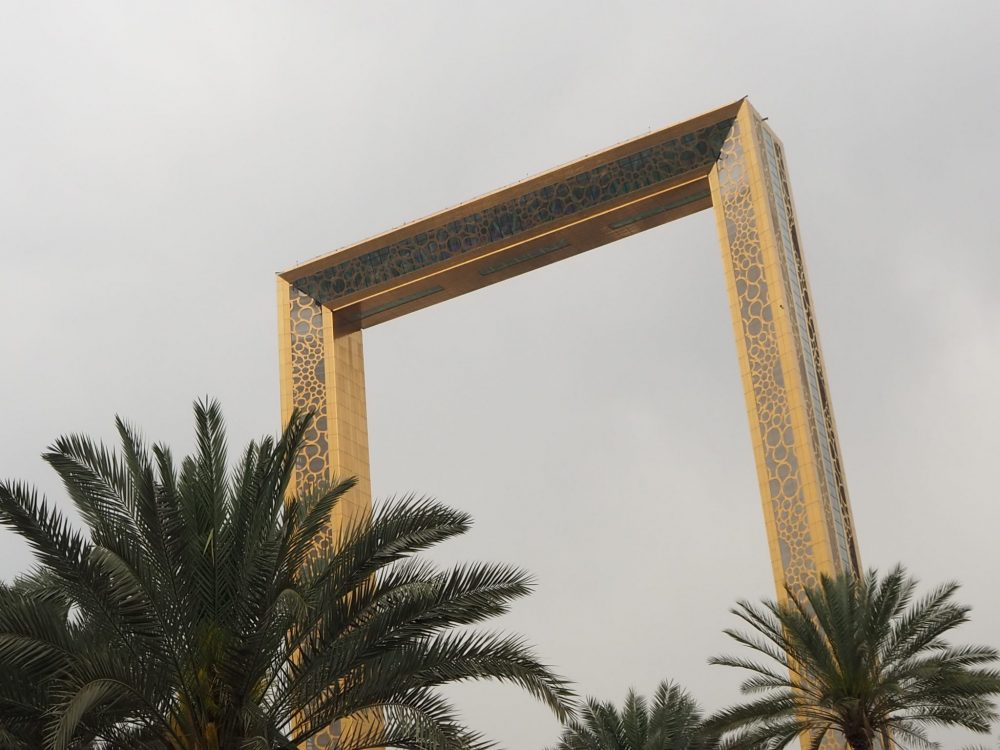 Tops of a few palm trees along the bottom of the picture. Behind, a large picture frame, gold colored. Gray sky visible through it and around it.