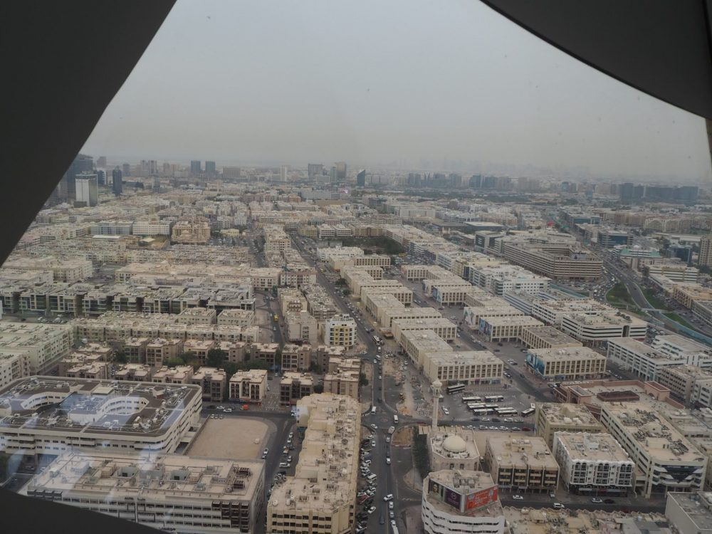 This is a predominantly light brown view, with neat blocks of low-rise apartments and straight streets dividing them. While the buildings are light brown, the sky is grey and the view gets pretty fuzzy in the distance from the pollution/dust in the air.