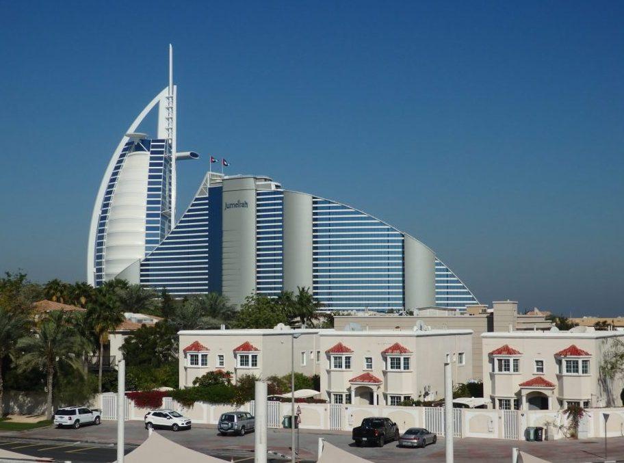 The Burj Al Arab behind the equally upscale Jumeirah Beach Hotel in Dubai.