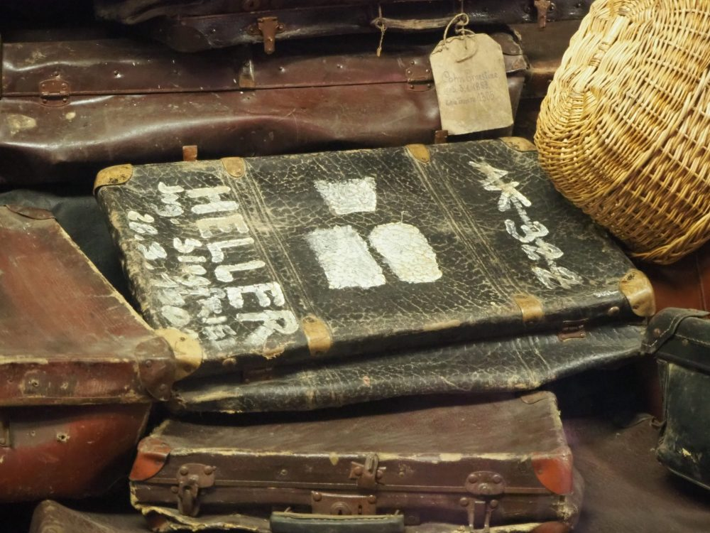 Just one suitcase in a very large pile of abandoned suitcases. I can make out the name Siegfried and HELLER and what I think is a birthdate: 28.3.1902. I dont know what the short word before Siegfried is, and I dont know what the crossed out AK 322 means.