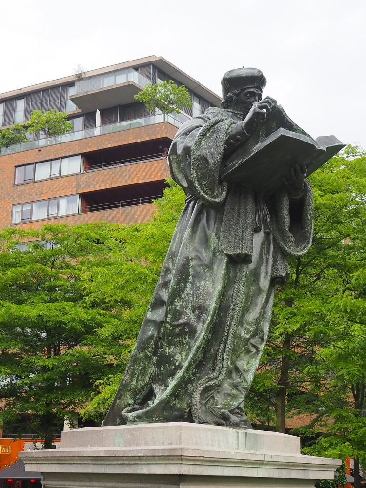 bronze full-size statue of Erasmus in robes, wearing a beret-like hat. He holds a large book and turns the page as he reads.