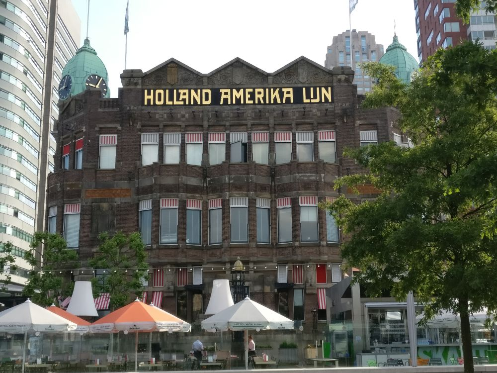 """The last stop on the Rotterdam walking tour: A reddish-stone 3-4 story building with a zig-zag decorative roofline and a small green cupola with a clock. Across the top, it reads """"Holland Amerika Lijn"""". IN front are cafe tables with umbrellas."""
