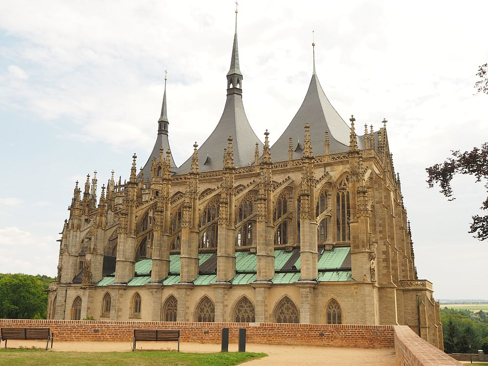 The side of the church shows gothic windows and a row of flying buttresses: 9 are visible in this photo. the roof has three pointed towers. Part of the Kutna Hora UNESCO site.