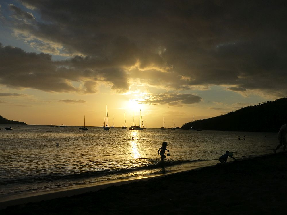 Malendure Beach at sunset. The sun, low in the sky, shows through clouds. Boats in silhouette on the water, and, nearer by, a child in silhouette, carrying a pail, runs out of the water.