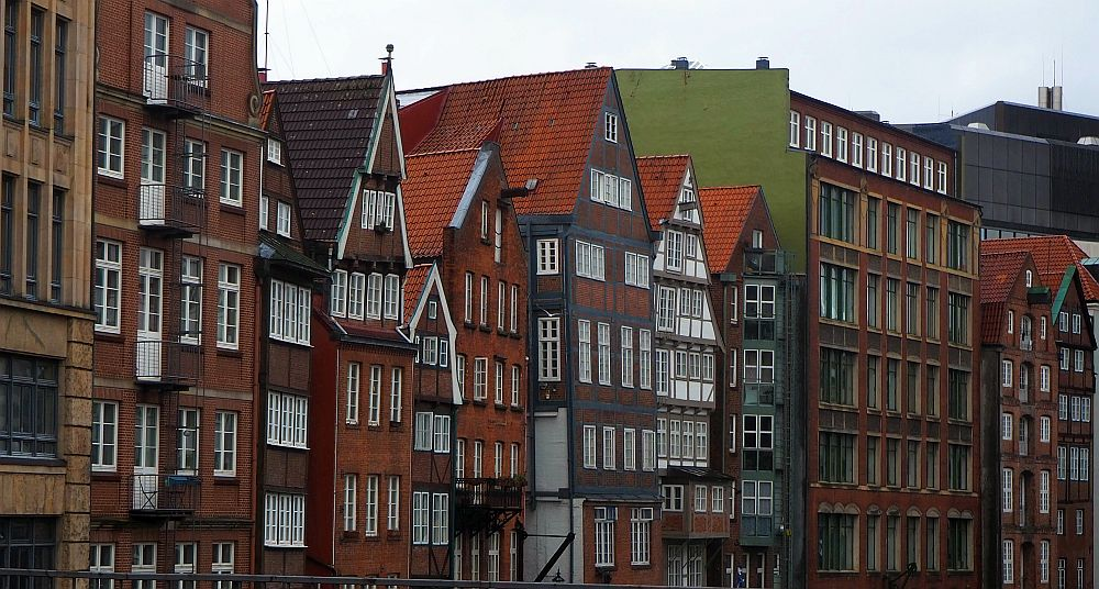 The builidings are tall and narrow with lots of windows, mostly red-brick. Some have half-timbered elements.