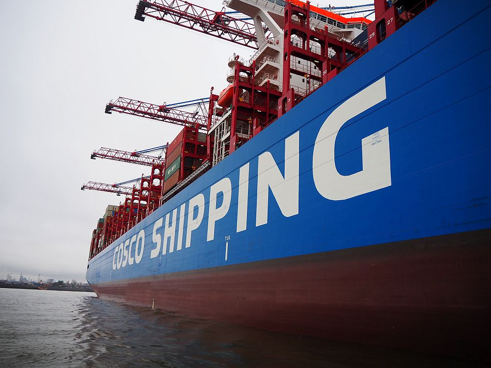 """A close view of the side of a container ship, reading """"Cosco Shipping"""" on the side, with large cranes extending over the side of the ship."""