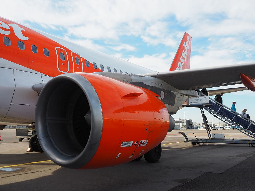 Passengers going down the stairs from the rear of an easyJet plane.