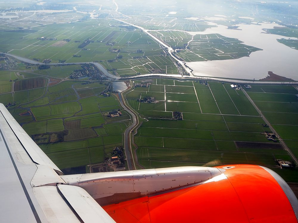 the view out of an easyJet flight shows a bit of the left engine and wing and, below, green fields edged by ditches.