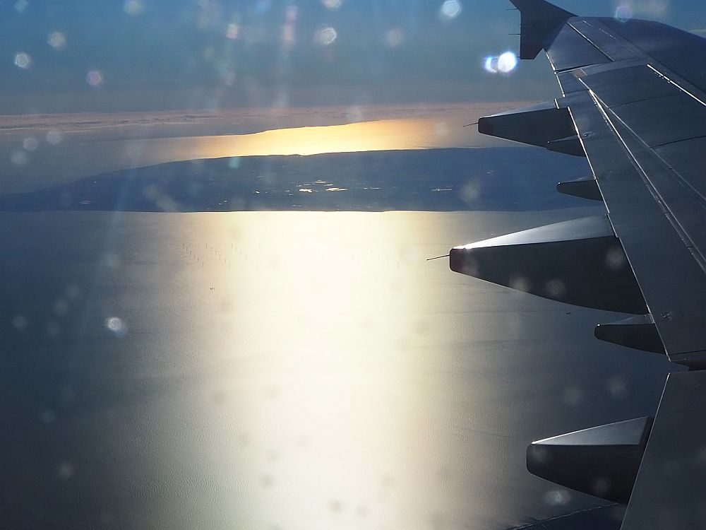 view from an airplane window, showing the sun on the water and an island in the distance, with the edge of the wing visible on the right.