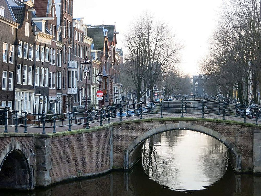 A typical scene in old Amsterdam: a canal, a small bridge over it, and Golden Age brick row houses along the canal.