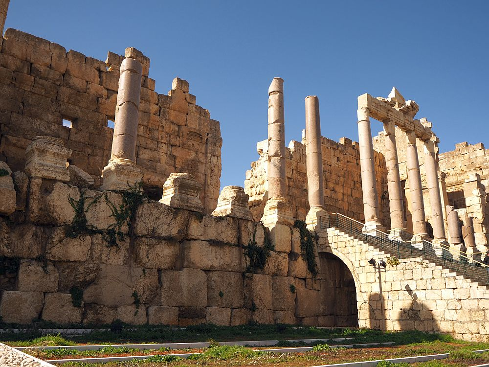 the entrance to the Baalbek ruins, and in particular the Temple of Jupiter has a few remaining pink granite columns in a row, at the top of a stone stairway. The bases of more pillars along the edge of the building remain. Behind that is a wall made of large stones that would have formed the back wall of the pillar-lined portico.
