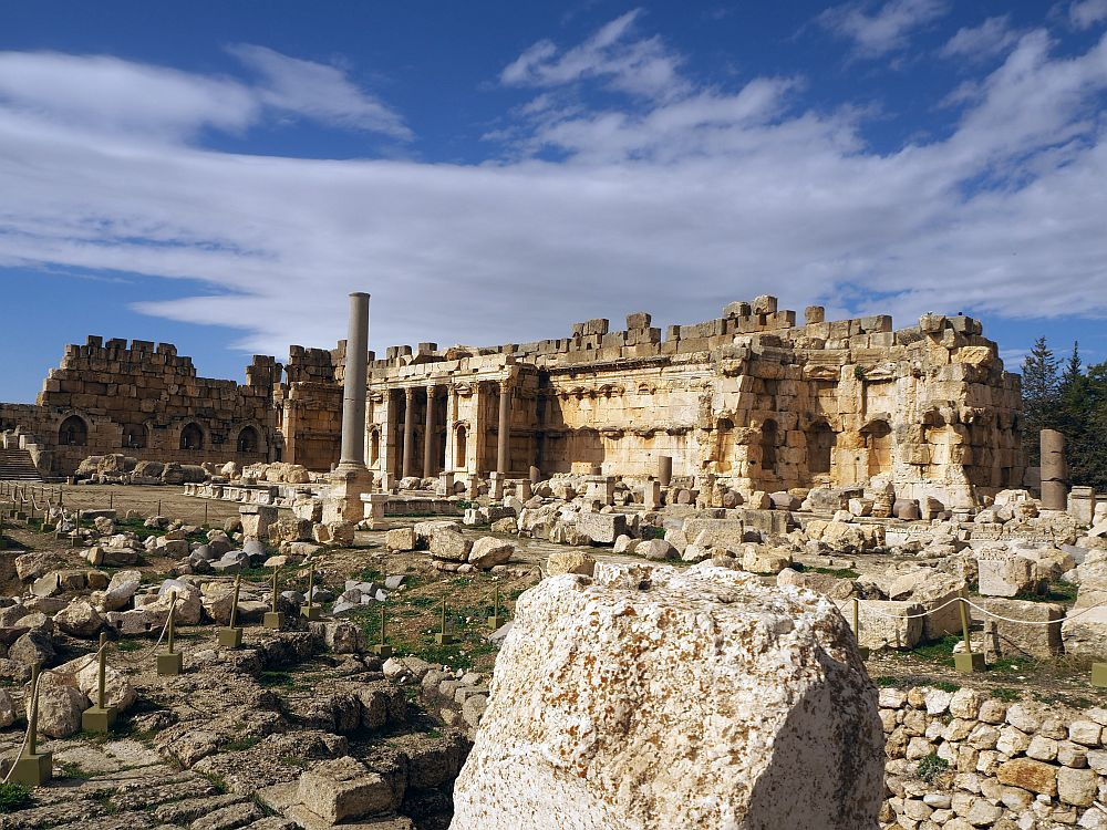 Nearby the ground is scattered with random pieces of rubble. In the background is an altar with pillars and a few extra rows of darker stone on top. At Baalbek ruins in Lebanon.