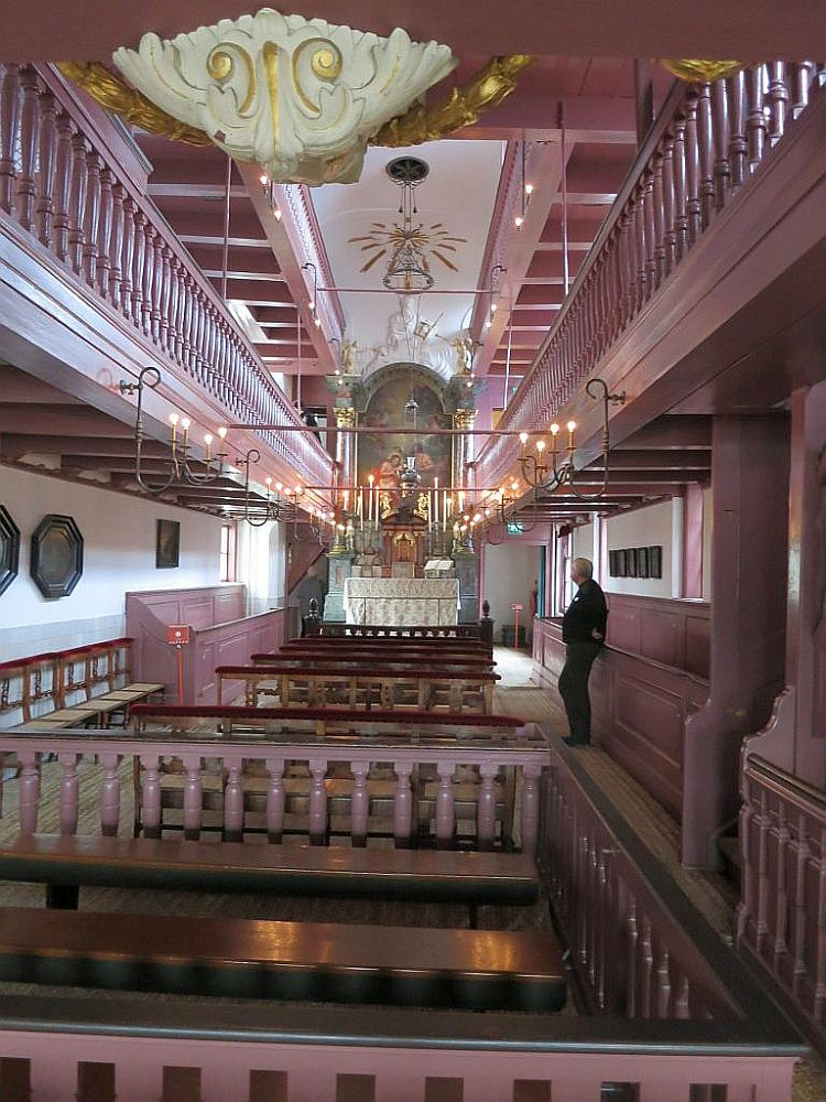 The church is a high and narrow space and mostly painted pink.