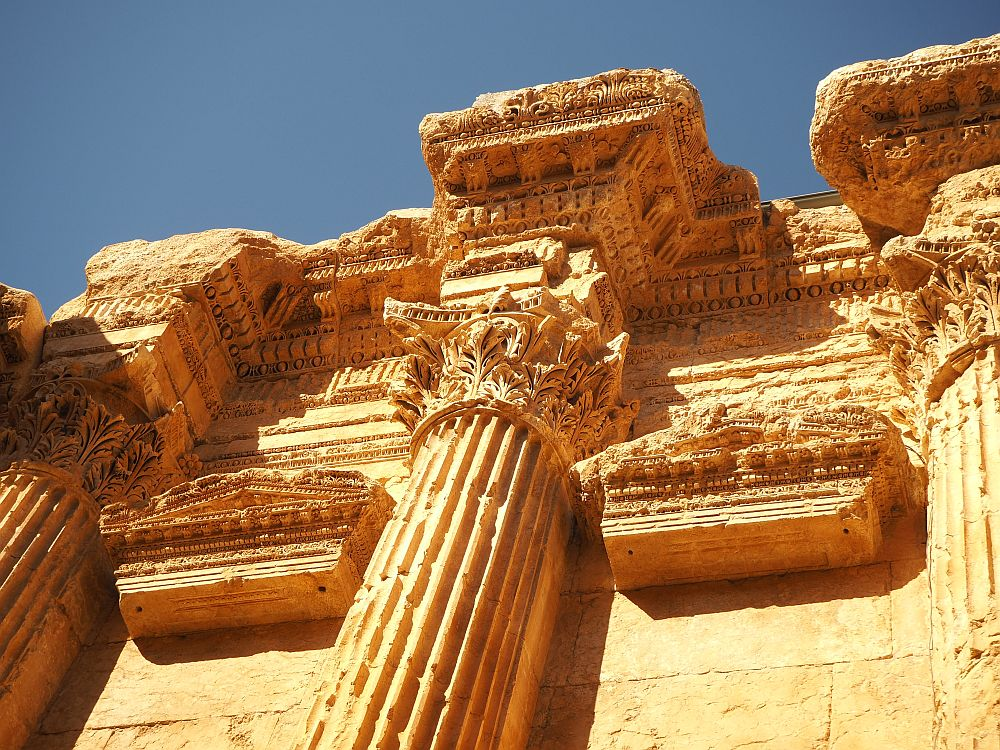 A very ornate Corinthian capital and more ornate stonework above it. Baalbek ruins in Lebanon.