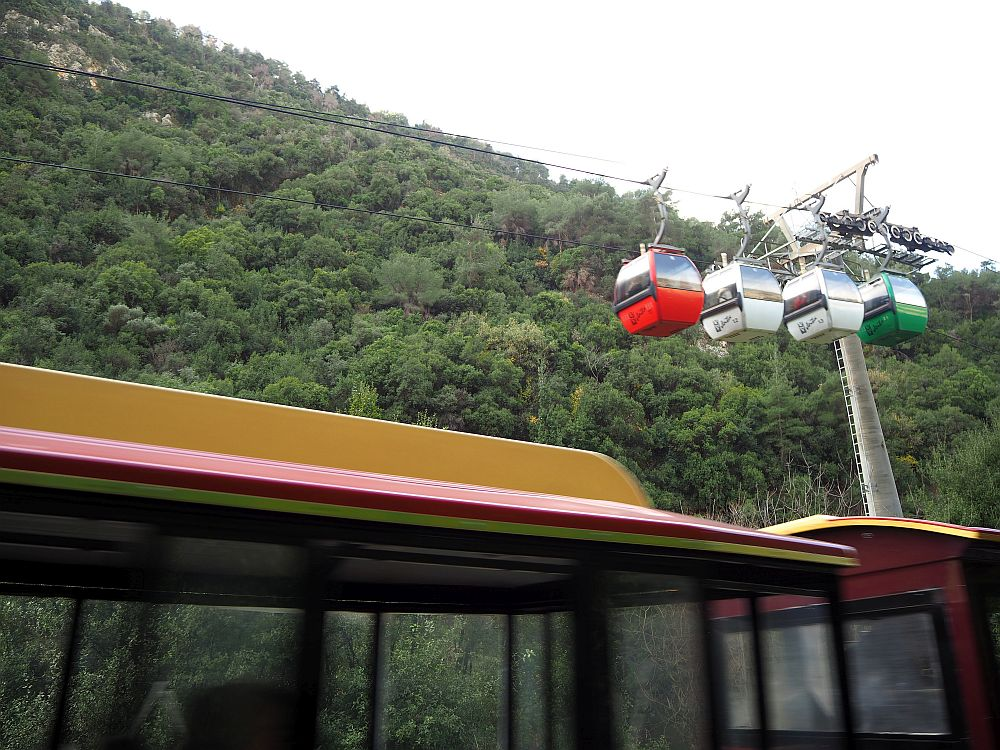 """In the foreground, a blurry roof of the """"train"""". In the background, four hanging gondolas on the ropeway cable."""