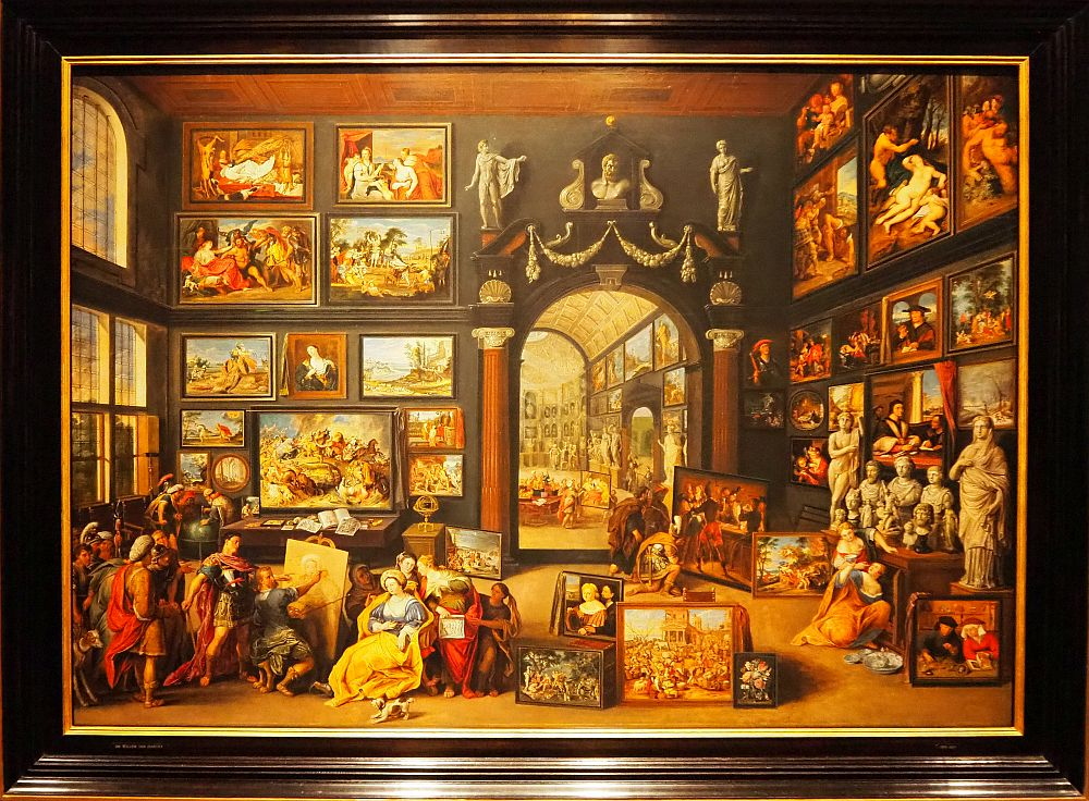 The painting shows an artist painting a portrait in a huge room whose walls are covered with paintings, done in remarkable detail.