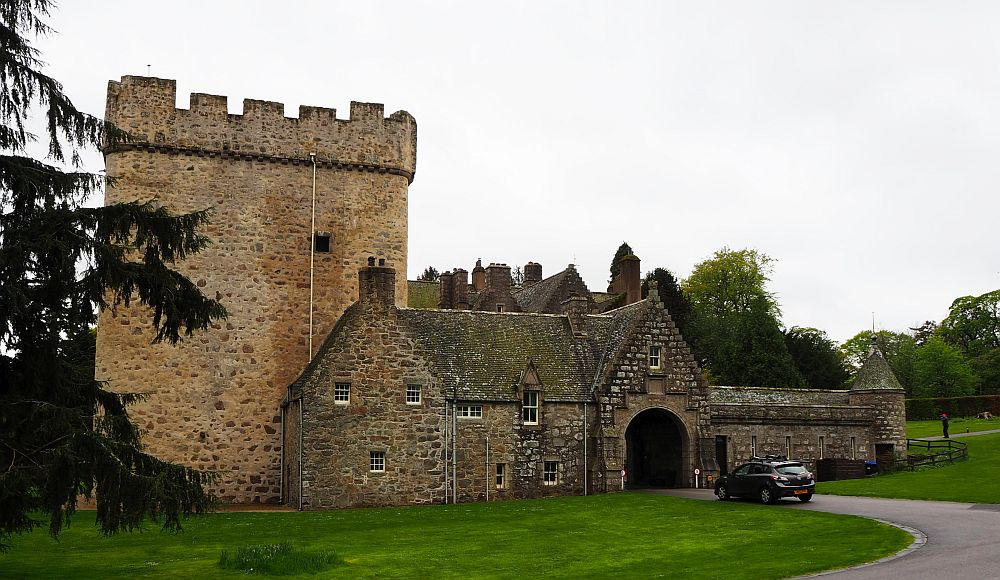 Drum Castle, is mostly low stone construction, with one squat tower on the left of the picture, crenellated at the top.