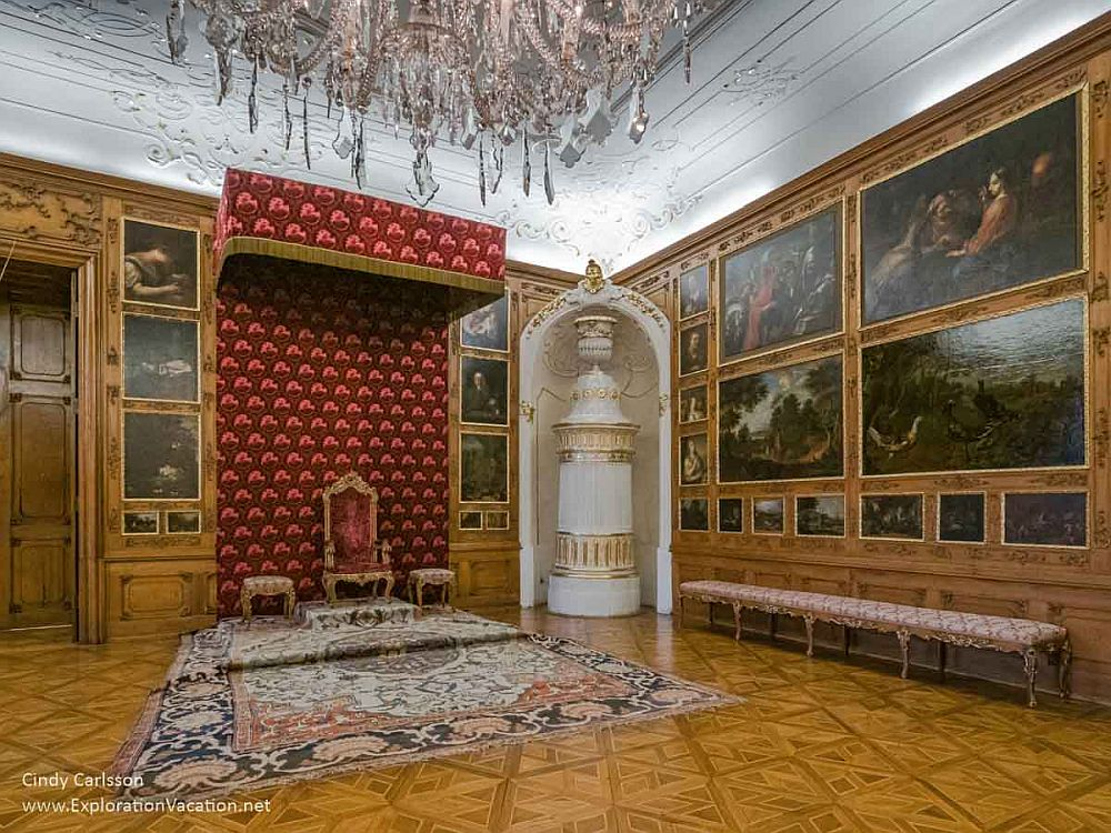 A throne on a raised platform on the far wall, with the side walls and ceiling ornately painted.