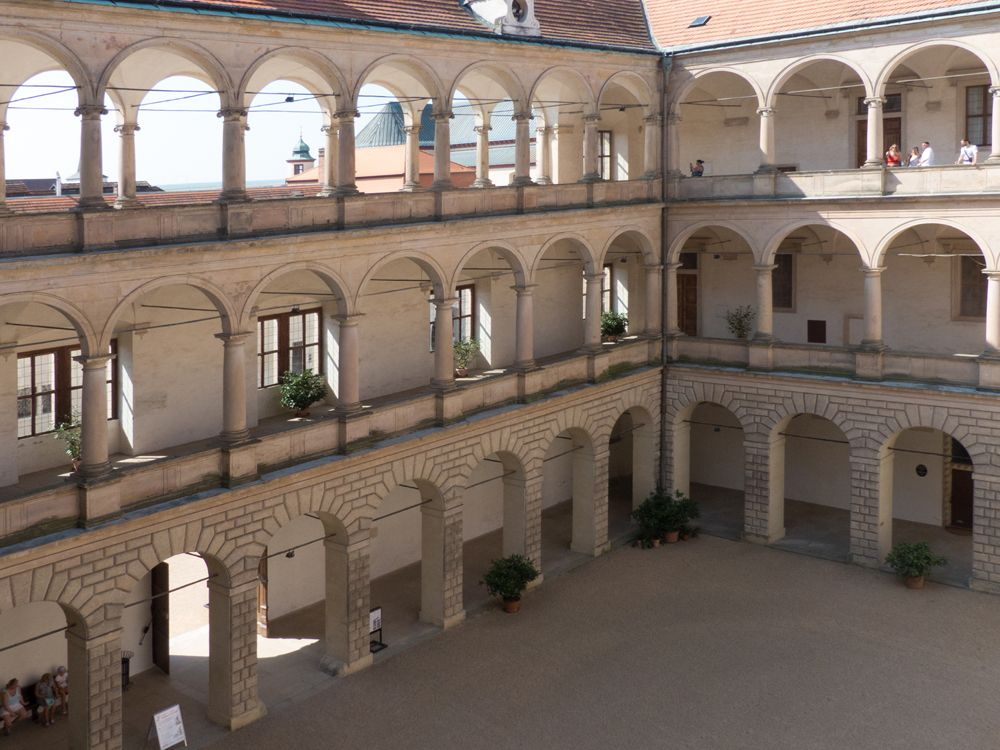The two sides of the courtyard shown in the photo are made up of columns, holding up arches. There are three rows of the columns and arches piled on top of each other.