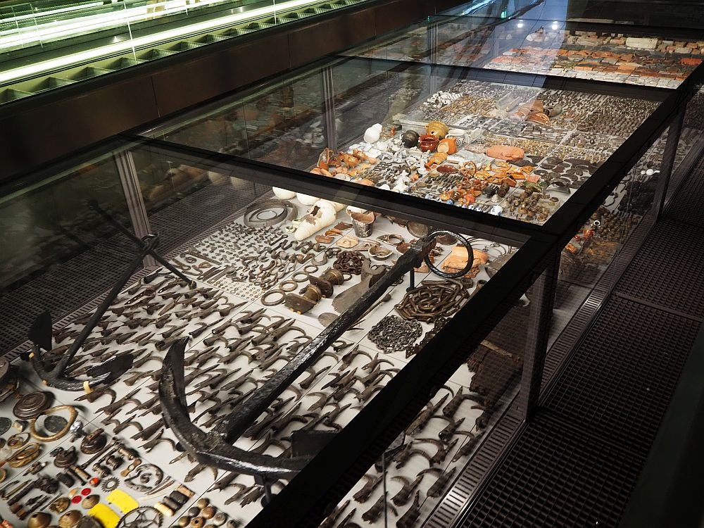 A glass-enclosed display case, with inbuilt lights illuminating the objects inside, closely packed together.