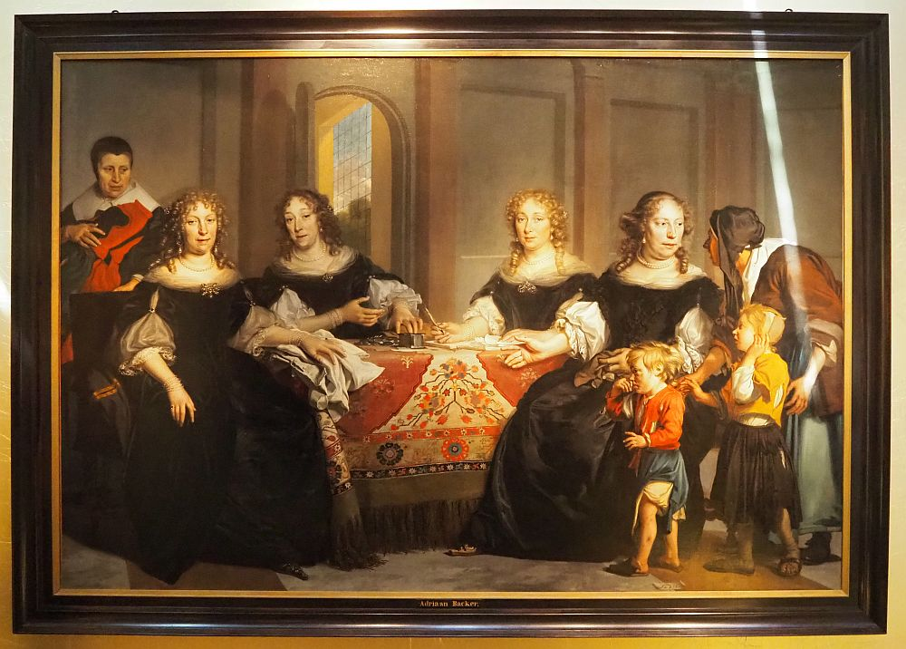 A group of four women sit at a table, dressed in black. A servant stands behind them holding the uniforms. Another servant stands with two orphans, bending to speak to one of the regents.