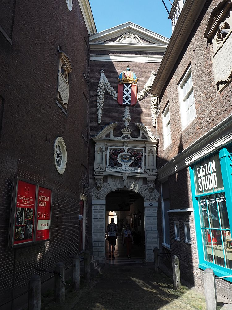Down a narrow alleyway, a gateway is visible that is the entrance to the Amsterdam Historical Museum. It is arched and rather ornate, with a distinct lean to the right.