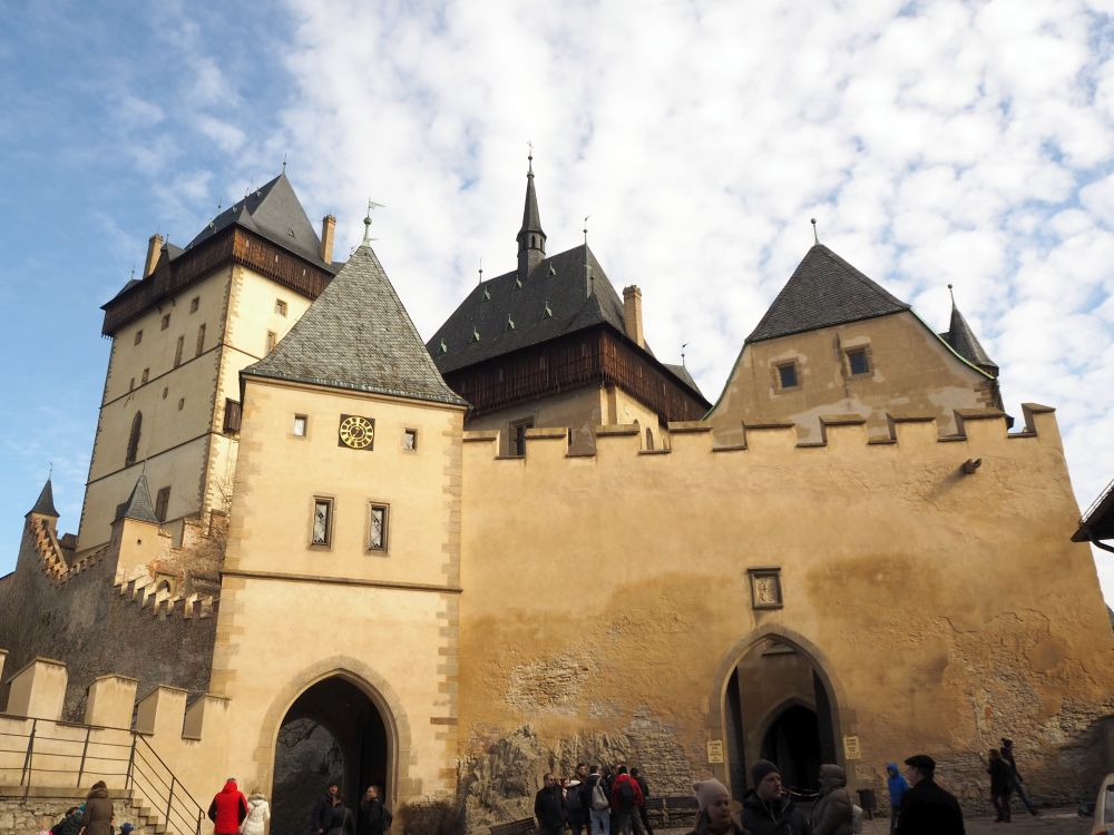 A large wall with crenellations and a gateway in its middle, and three towertops visible behind it.