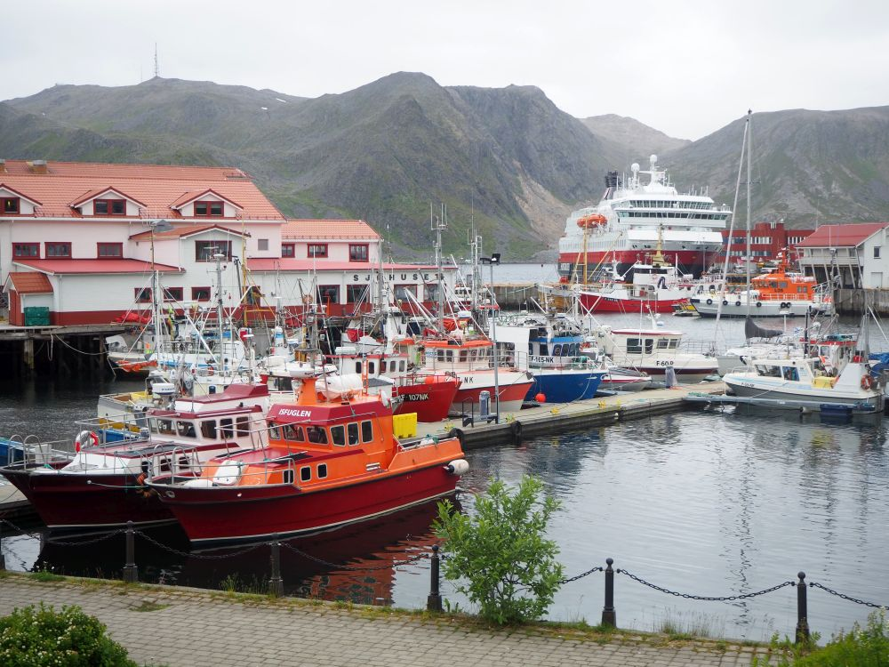 A cluster of small fishing boats moored on a dock, with the Hurtigruten ship visible in the background, and rocky, bare mountains visible beyond that. Hurtigruten review.