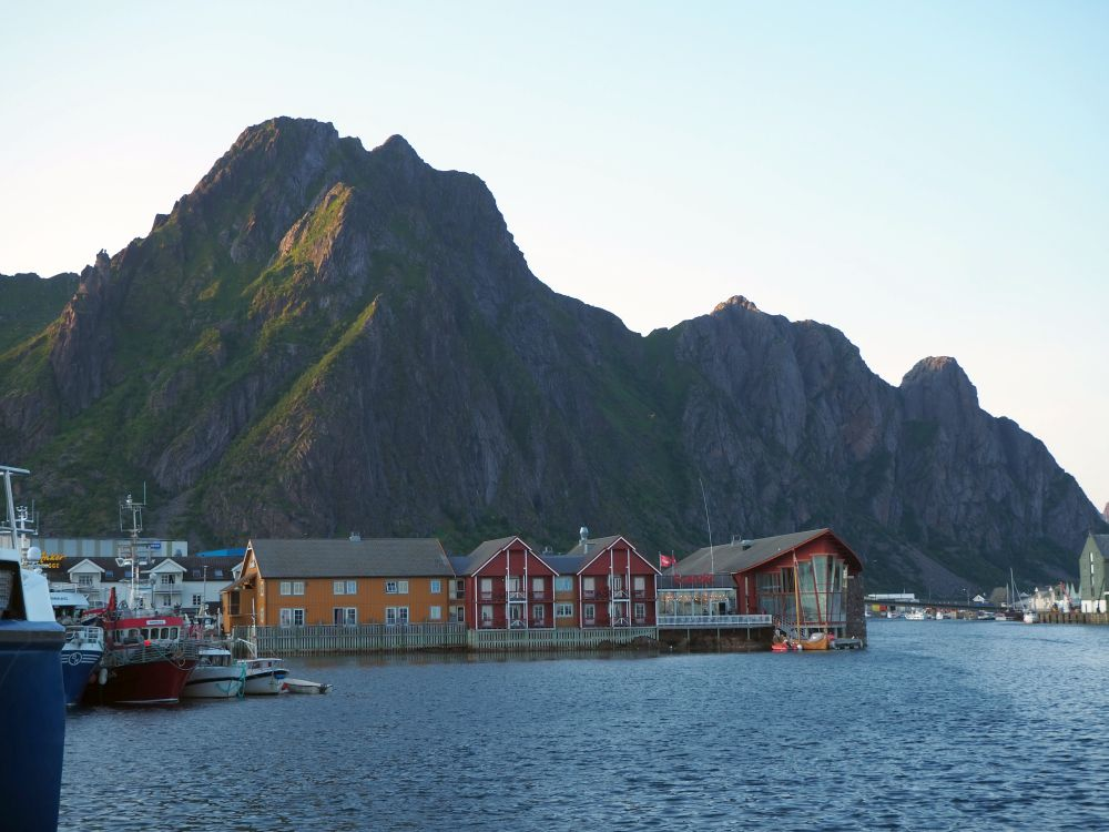 A line of buildings on a pier with peaked roofs in orange and red. Very rocky mountain behind.