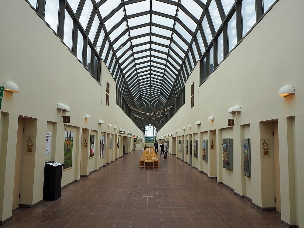 Among the things to do in Rovaniemi is to visit Arktikum. Ahead is a long, straight hallway with doors lining both sides. Above, the second story is an arched glass roof, the whole length of the hall. At the very end, far in the distance, a glass window is visible.