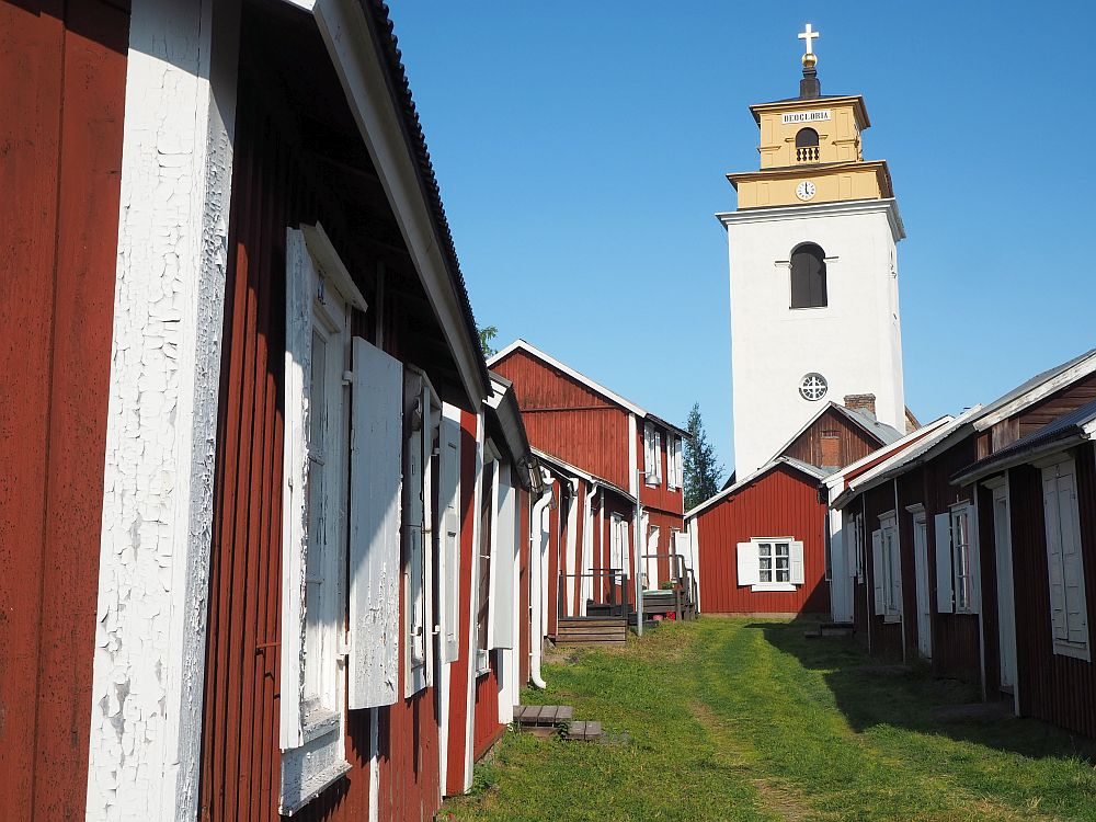 """Pretty little red houses with white trip line a grassy """"street. At the end, a tall church tower in white with a yellowish top."""