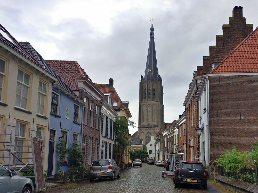 A view down a cobbled street with pretty row houses down each side, some red brick, some painted various colors. At the end of the street, a tall church tower in brown stone.