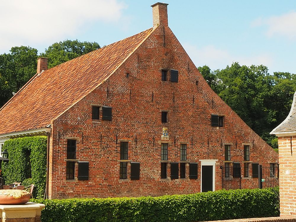 The photo of Het Schathuis at Menkemaborg in Uithuizen shows the side of the building: a triangular shape with a flat redbrick face. Small windows pierce it here and there. A small part of the front of the building is visible, covered in ivy, and just on the edge of the picture one of the chairs of the outdoor part of the cafe is visible.