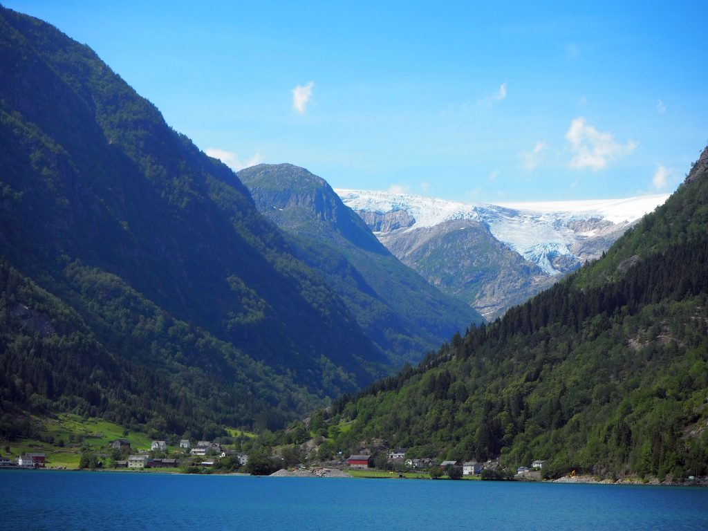 A view in Norway: blue water in the foreground, a small cluster of houses on the shore. On either side of the village, huge tree-covered mountains. In the background, even higher mountains, covered in snow.