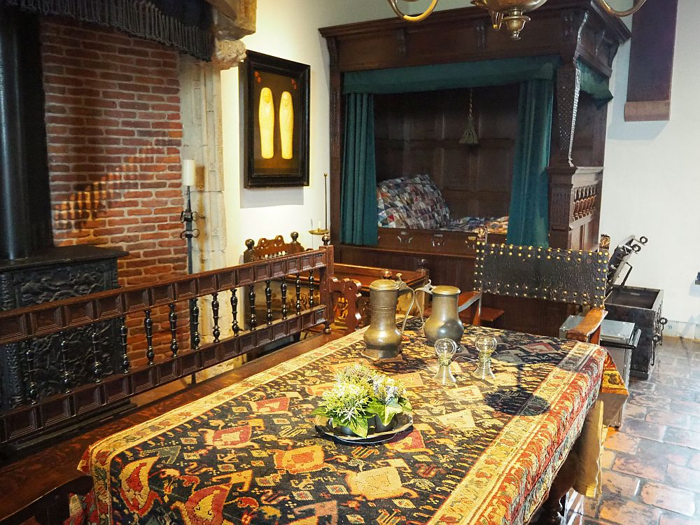In the foreground, a table covered by a colorful rug. On that are two glasses and a couple of bronze pitchers as well as a flower centerpiece. On the left only a corner of the large fireplace is visible. In the background is a canopied box bed and, beside it, a small crib.