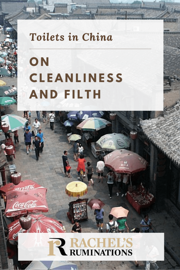 Pinnable image Text: Toilets in China: On cleanliness and filth Image: a view from above of a street lined with simple brown brick buildings. Umbrellas cover street stalls on both sides of the street and people walk down the middle between them.