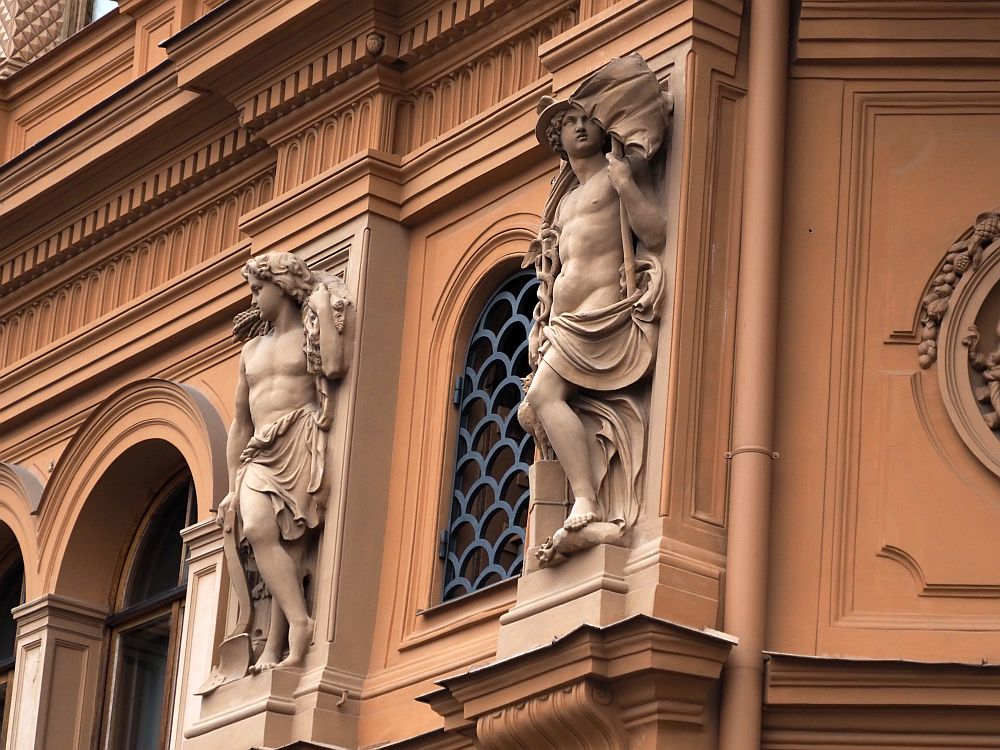 Between arched windows are two classical-style statues, both of muscular young men, naked except for draped cloths around their waists.