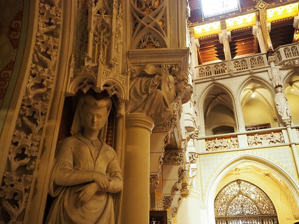 In the foreground, a very complicated carved side of a doorway with an image of a human in front: a woman wearing a medieval headdress and dress. In the background, balconies overlooking the courtyard: each opening has a gothic arch and between the arches are more statues.