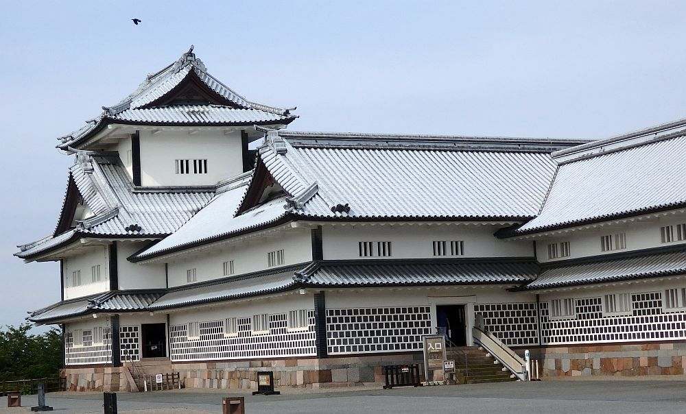 One end of the building shows the visitors' entrance up a short flight of stairs. The building is about 4 stories tall. The outside is mostly plastered in white, though the bottom floor shows neat rows of brown stones.