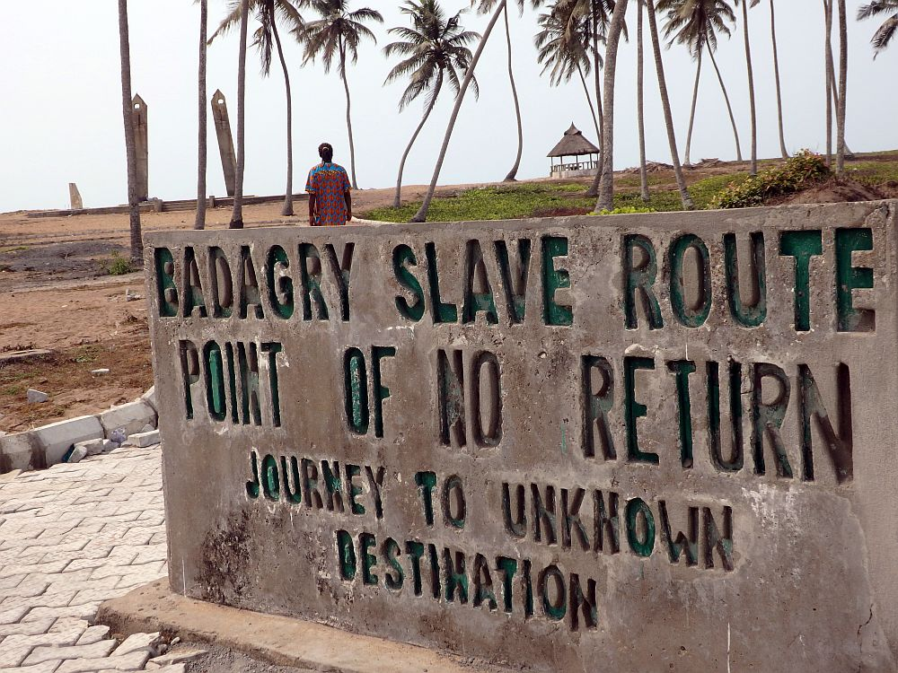 In the foreground, a concrete sign carved with capital letters reading: BADAGRY SLAVE ROUTE POINT OF NO RETURN JOURNEY TO UNKNOWN DESTINATION Beyond the sign is a flat piece of land, partly brown dirt and partly grass-covered, with a few tall palm trees spaced over it. Beyond them is the monument, just two concrete poles, slightly leaning inward, each with a round hole at its tip. A man walks toward the monument; only his upper body is visible above the sign.