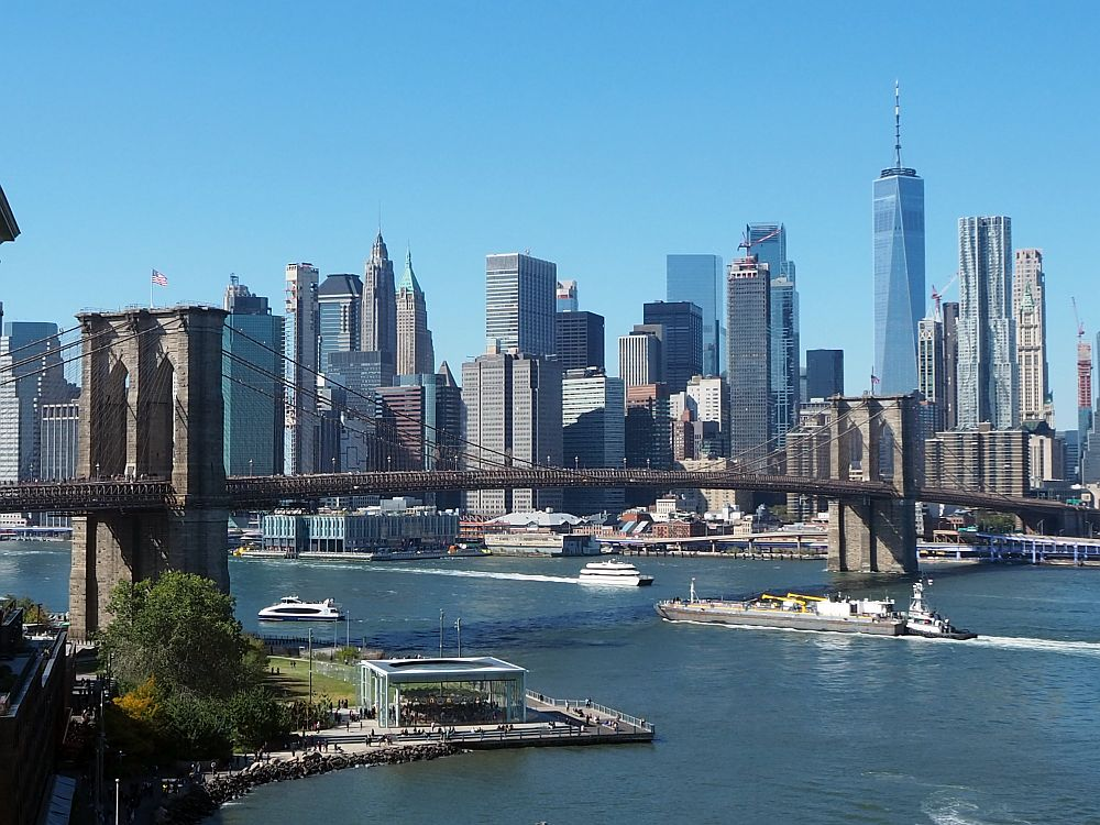 Similar to the view above of the lower Manhattan skyline, this one shows both support towers of the Brooklyn Bridge spanning the river. A number of boats pass under it. Jane's Carousel is visible below the nearer tower.