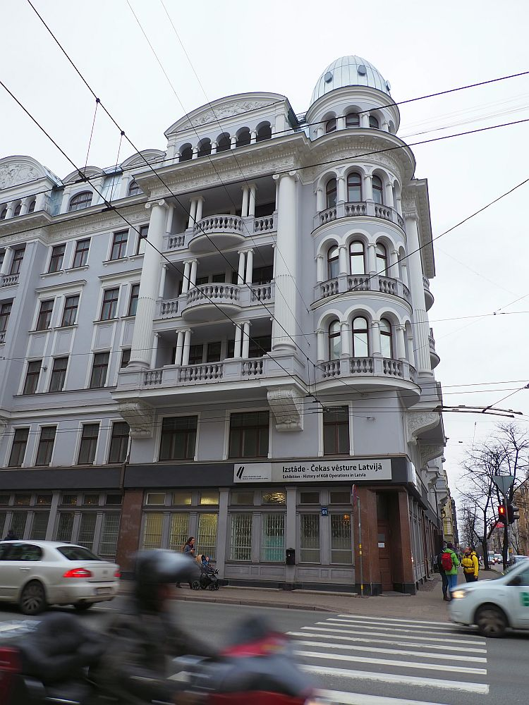 The building is quite elegant: painted grey with white trim, about 6 stories high. On the corner is a tower of sorts, so all of the apartments above the ground floor had a rounded room with arched windows. ON the side facing the main street each floor has a balcony with a decorative railing, and pillars. The one on the top floor has a row of arches held up by pillars. The entrance to the museum is on the corner in what used to be a storefrunt.